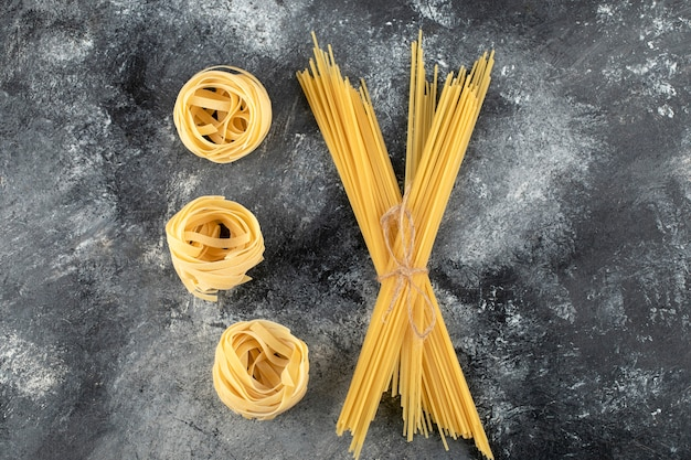 Dry tagliatelle nests and spaghetti on marble surface