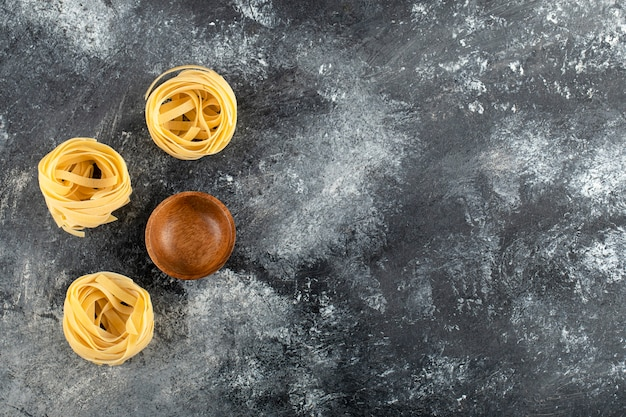 Dry tagliatelle nests and wooden bowl on marble surface