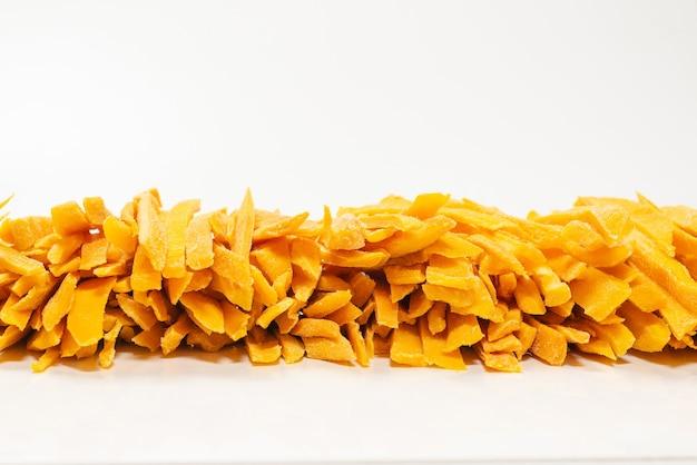 Сухие вкусные ломтики манго в качестве фона. вид сверху.
