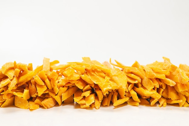 Dry tasty mango slices as a background. top view.