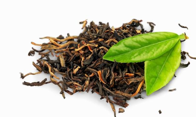 白で隔離される乾燥したお茶と新鮮な緑の葉