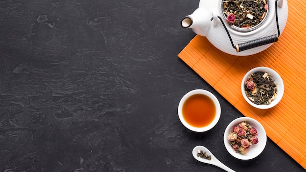 Dry tea ingredients in ceramic bowl with tea pot on placemat over black surface