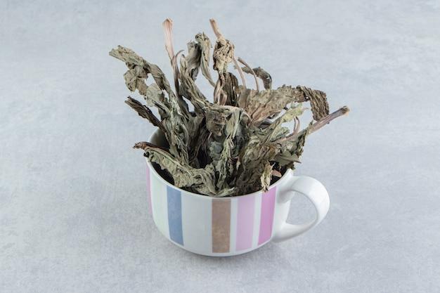 Dry tea leaves in ceramic mug.