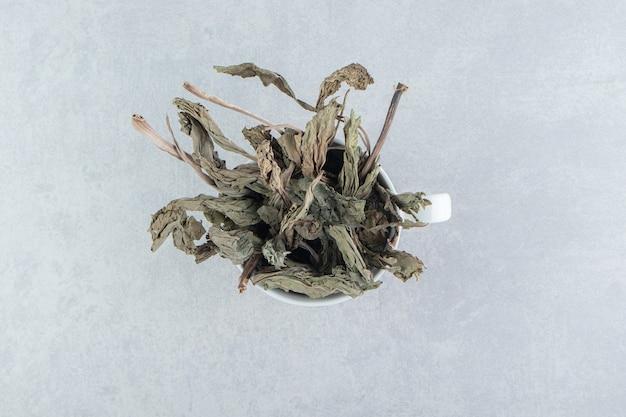 Dry tea leaves in ceramic mug