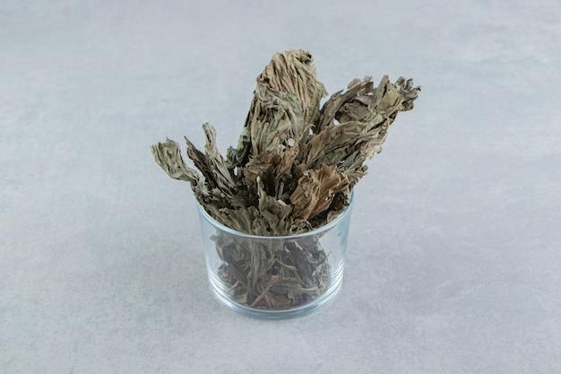 Foglie di tè asciutte in vetro sulla tavola di pietra.