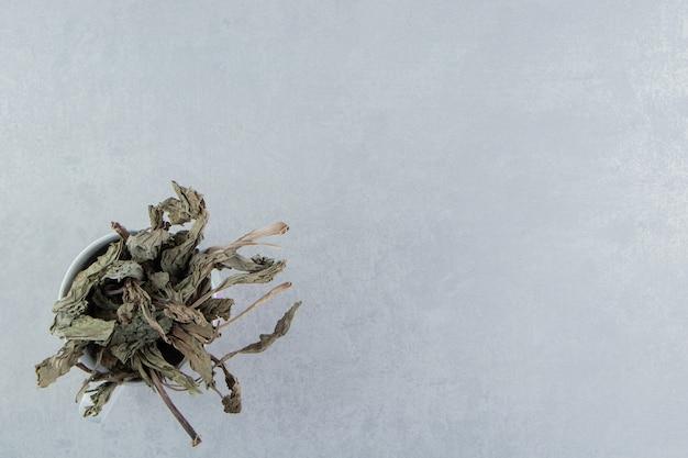 Сухие чайные листья в керамической кружке.