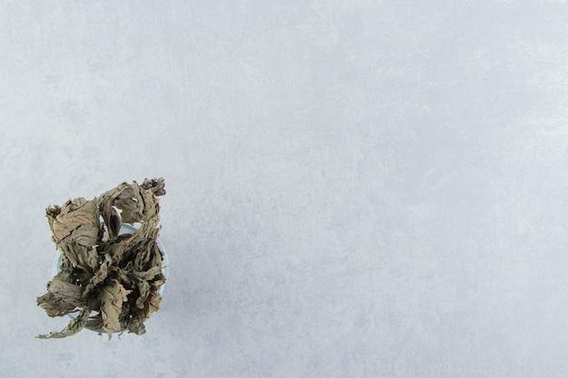 Сухие чайные листья в стекле на каменной поверхности