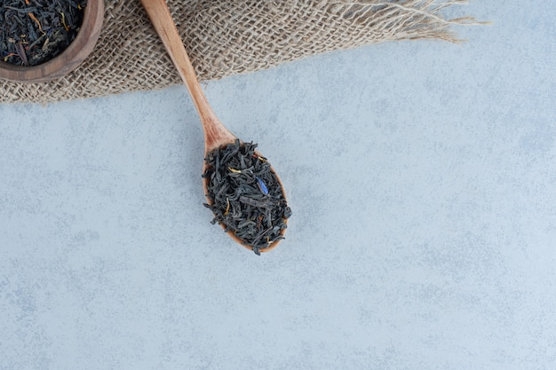 木製のボウルに茶葉を乾かし、大理石のタオルにスプーンでかけます。