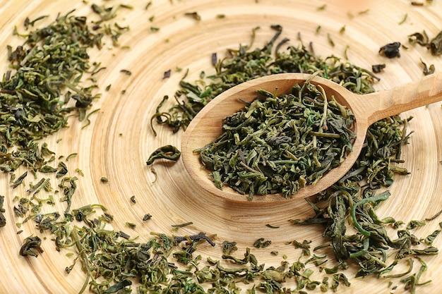 Сухие чайные листья в деревянной ложке на столе