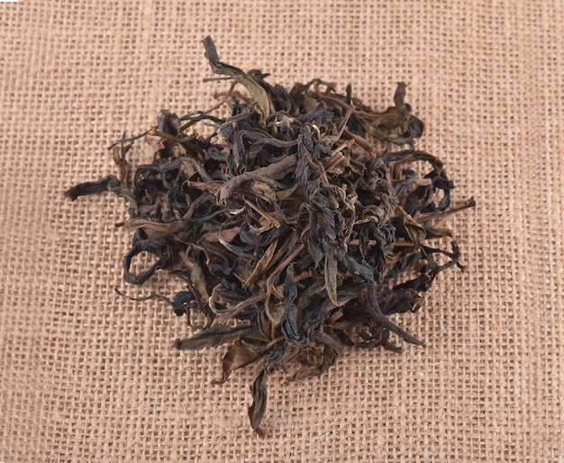 Dry tea leaves isolated on burlap background.
