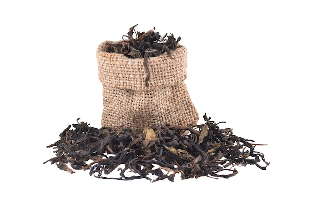 白い背景で隔離の黄麻布バッグの乾燥茶葉。