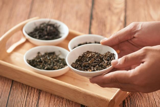 Сухие чайные листья на тарелке в руке человека
