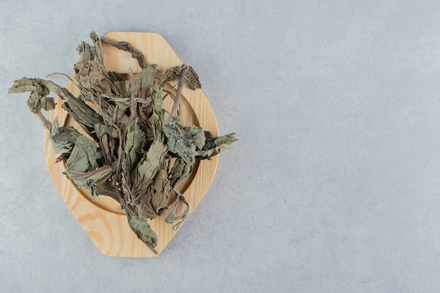 Сухие чайные листья на деревянной тарелке.