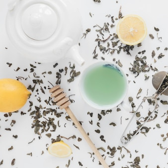 Dry tea leaves; tea strainer; lemon; fresh green tea; and teapot on white backdrop