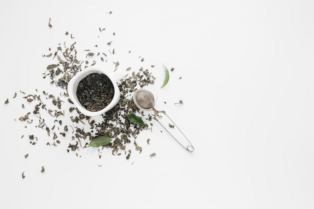 Dry tea leaves with coffee leaves and tea strainer on white backdrop