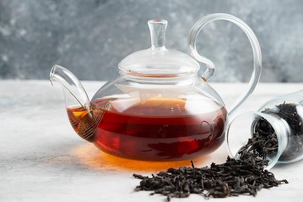 Foglie di tè secche con teiera su marmo.