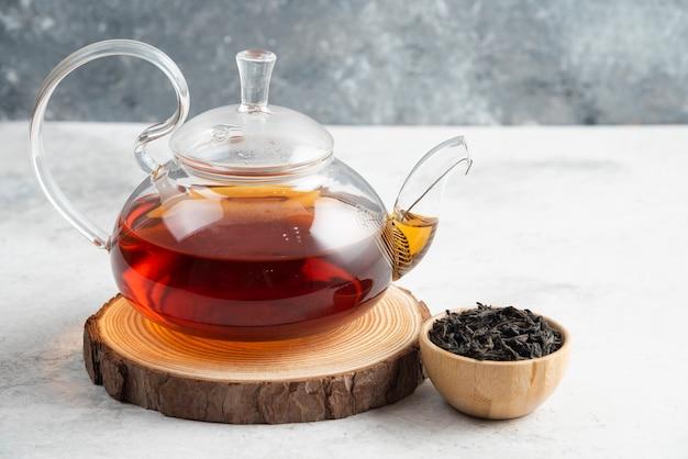 Foglie di tè secche con teiera su tavola di legno.