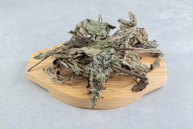 Dry tea leaves on wooden plate.