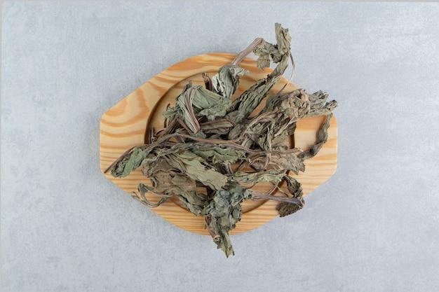 Dry tea leaves on wooden plate