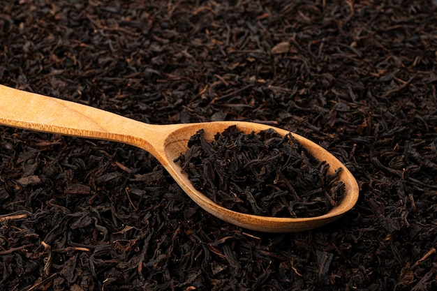 Dry tea leaves in wooden spoon over tea leaves background or texture