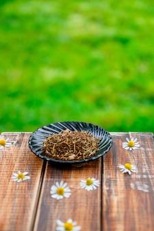 カモミールの庭の花と自然の木製テーブルの上の皿にお茶を乾燥させます。お茶 。茶葉。閉じる