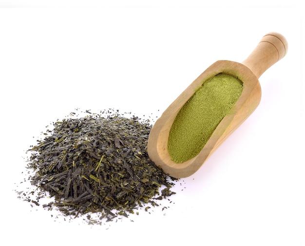 Сухой чай или порошок зеленого чая на белом фоне