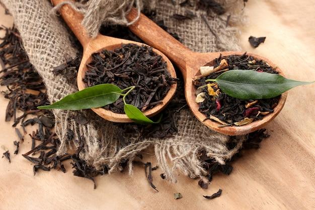 Сухой чай с зелеными листьями в деревянных ложках на деревянном пространстве