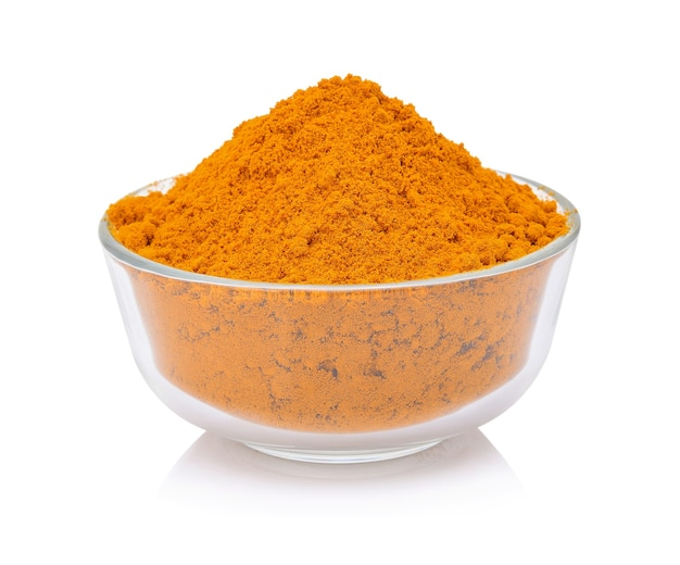 Dry turmeric powder in white bowl isolated