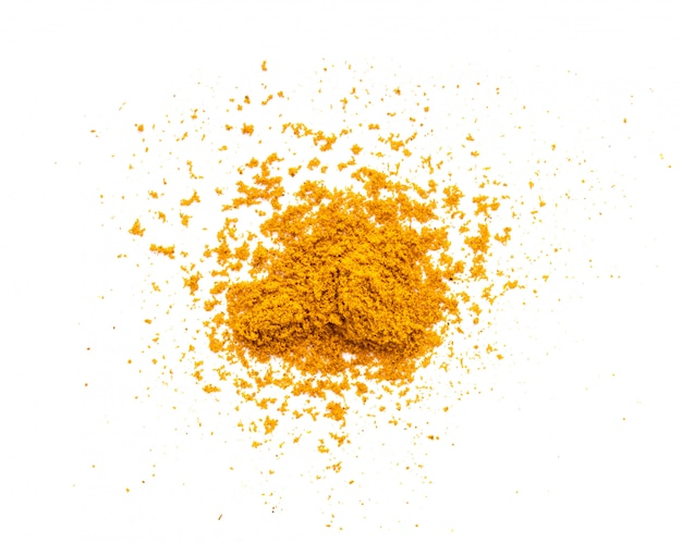 Dry turmeric powder on white table.