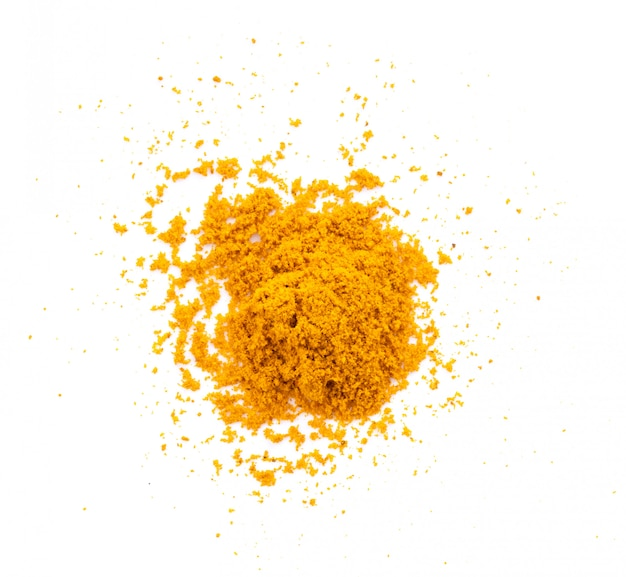 Dry turmeric powder on white wall.