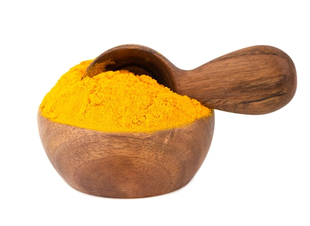 Dry turmeric powder in wooden bowl and spoon, isolated on white background.