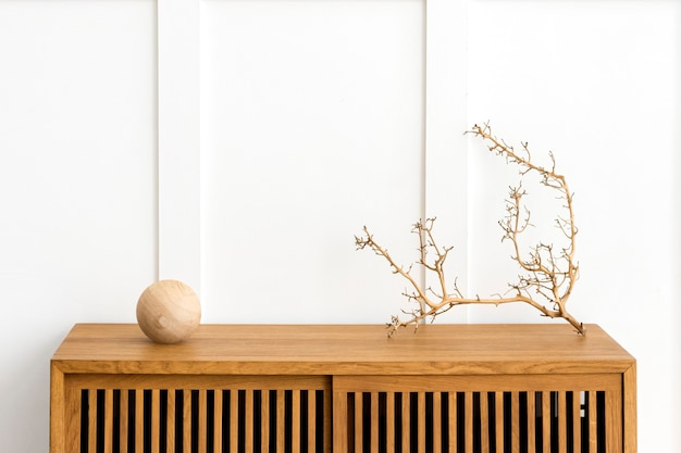Dry twig on a wooden cabinet in a white room