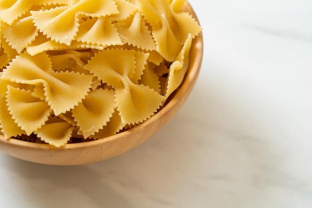 Сухие сырые макароны фарфалле в деревянной миске
