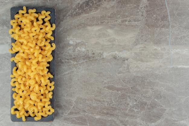 Сухие сырые макароны на черной тарелке