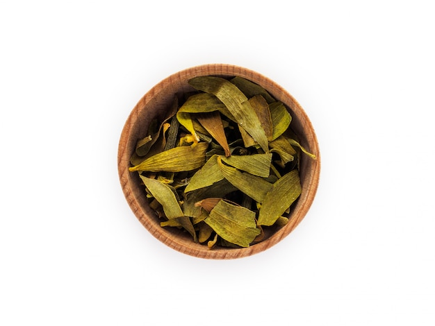 Dry viscum leaves in wooden cup on white