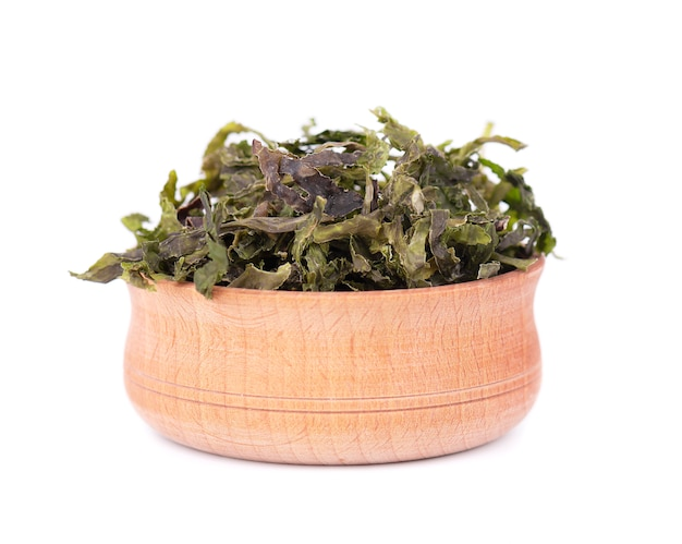 Dry wakame seaweed in wooden bowl, isolated on white. sea kale, asian dry food.
