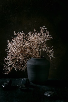 Dry white flowers branch in black ceramic vase on black wooden table with decorative stones. dark still life. copy space.