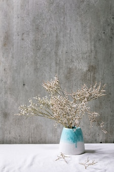 Dry white flowers branch in white ceramic vase on white linen tablecloth with gray wall behind