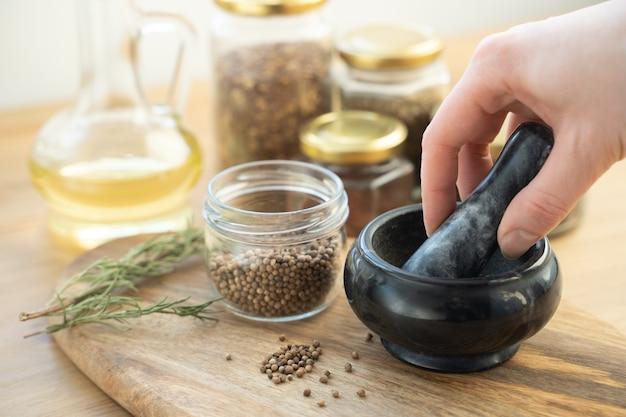 インドのケララ州にあるヴィンテージグラインダーの石臼と乳棒を使用して、伝統的なキッチンでコリアンダー全体を粉砕して粉末にします。ホットでスパイシーなグレイビーカレー、料理、料理のための自家製インドのスパイス。