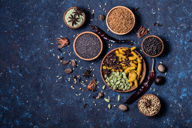 Dry whole warming indian spices in wooden bowls