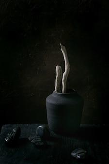 장식 돌으로 검은 나무 테이블에 검은 세라믹 꽃병에 마른 나무 가지. 어두운 정물. 공간을 복사하십시오.