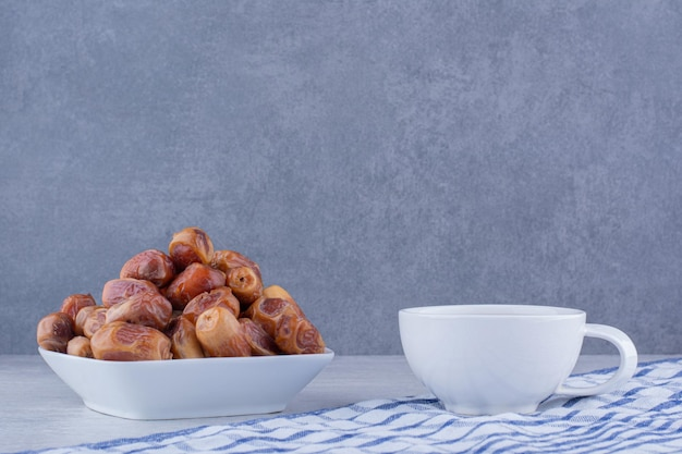 Dry yellow dates in a cup on concrete background. high quality photo