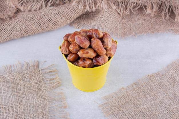 コンクリートの背景にカップで乾燥した黄色のナツメヤシ。高品質の写真