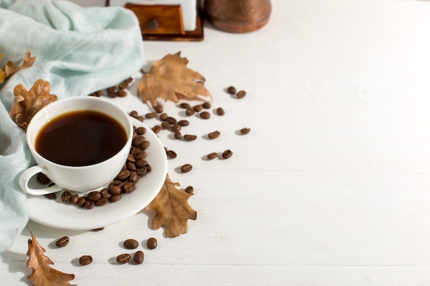 Dry yellow leaves, blue scarf, coffee grains and a cup on a white table, morning start day. autumn mood background, copyspace, flat lay.