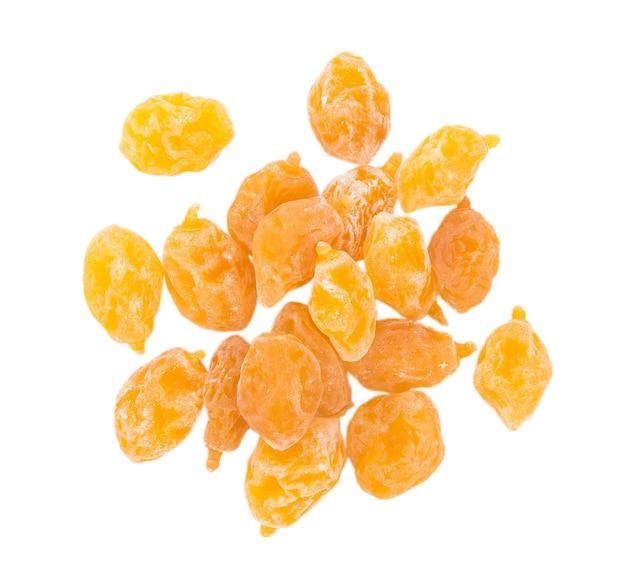 Сухие желтые сливы на белой поверхности