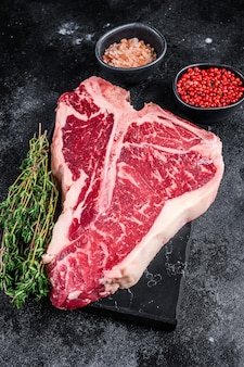 Dryaged raw tbone or porterhouse beef meat steak with herbs and salt.