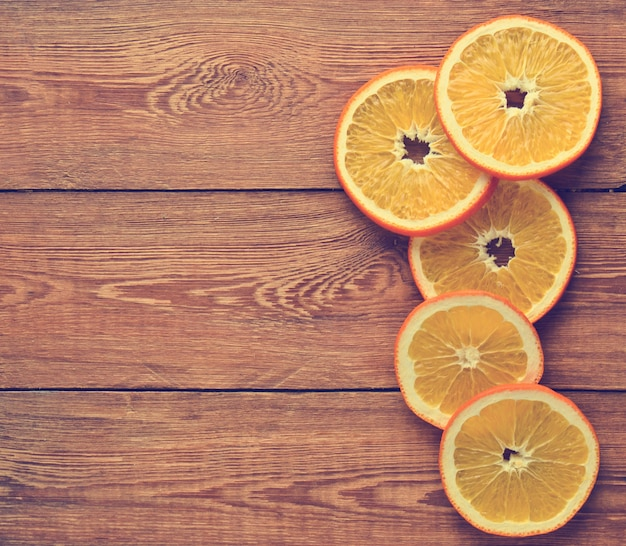 Dryed orange slices on a wooden surface. top view