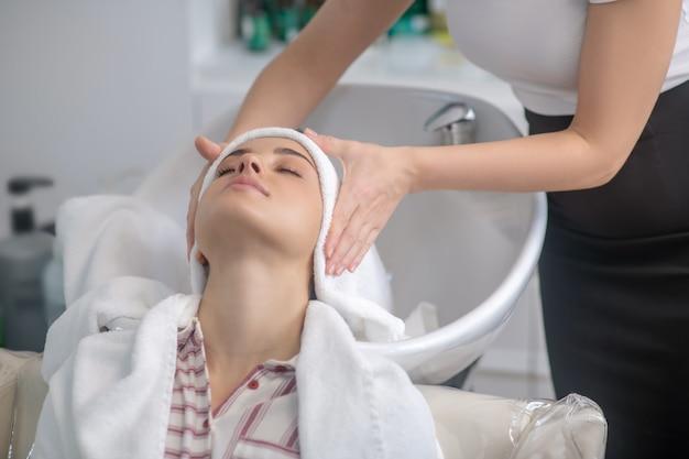 髪を乾かします。クライアントの髪をタオルで乾かす美容師