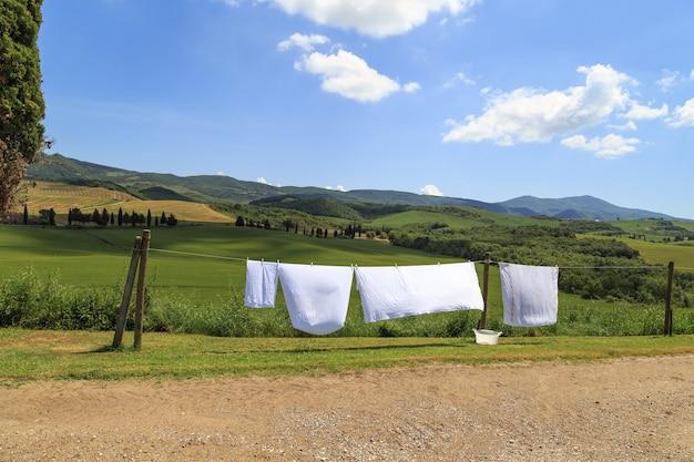 투스카니 농업 관광 이탈리아의 밝은 태양 아래 들판에서 린넨 건조