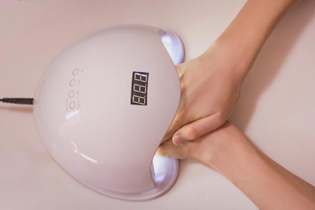 紫外線ランプで爪を乾かす